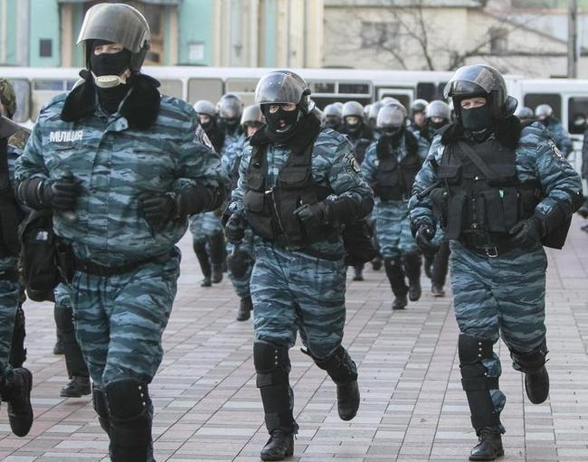 Police run in front of the Parliament building during a demonstration in support of EU integration in Kiev
