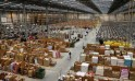 A member of staff pushes a trolley as he collects orders at the Amazon fulfilment centre in Peterborough