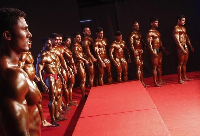 Competitors stand on a stage during a bodybuilding competition in Mumbai
