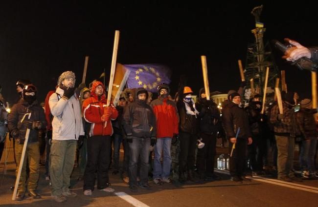 Protesters with wooden sticks line up at a barricade at Independence Square in Kiev