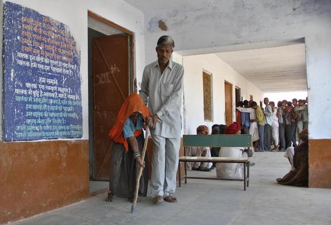 An elderly woman is helped by her son after she cast her vote during the state assembly election in Birchiwayas village