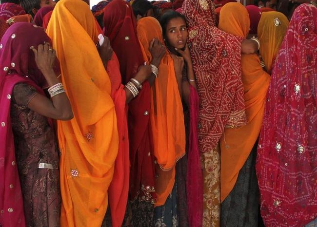 Women line up in a queue outside a polling booth to cast their vote during the state assembly election in Birchiwayas village