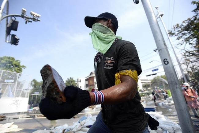 An anti-government protester holds a rock to throw at Thai riot police as they attempt to remove barricades outside Government House in Bangkok