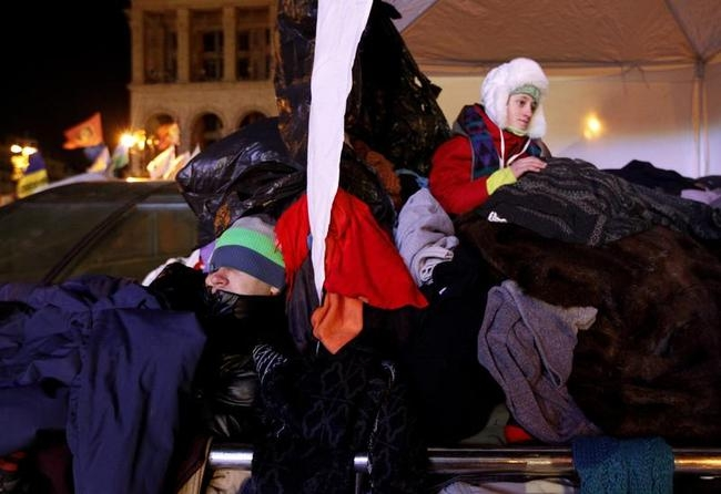 A man sleeps in a pile of donated clothes near a barricade at Independence Square in Kiev