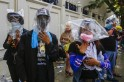 Anti-government protesters use plastic bags to cover their heads during a clashes with the police at the metropolitan police headquarters in Bangkok