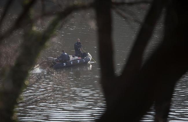 Police in a boat drag the Harlem River for bodies at the site of a Metro North train derailment in the Bronx borough of New York