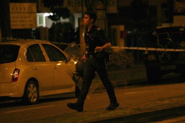 A police officer walks with a riot shield following a riot in Singapore