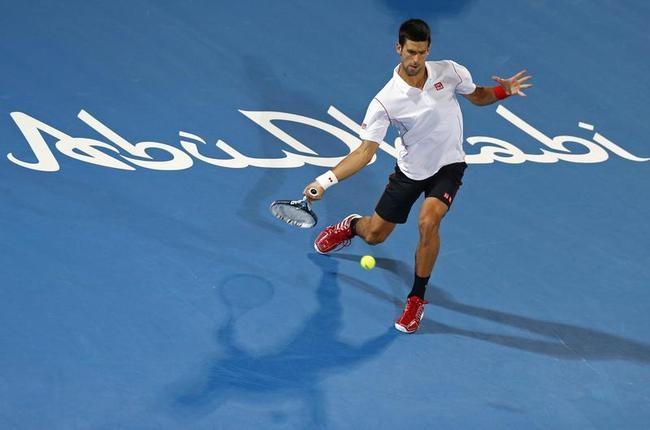 Novak Djokovic hits a return to Jo-Wilfried Tsonga during their semi-final tennis match at the Mubadala World Tennis Championship in Abu Dhabi