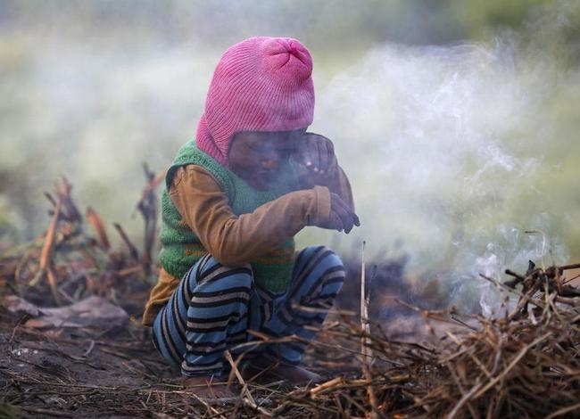 A boy wipes his eye as he sits near twigs which were set on fire by his parents to warm themselves at a vegetable field early morning in New Delhi