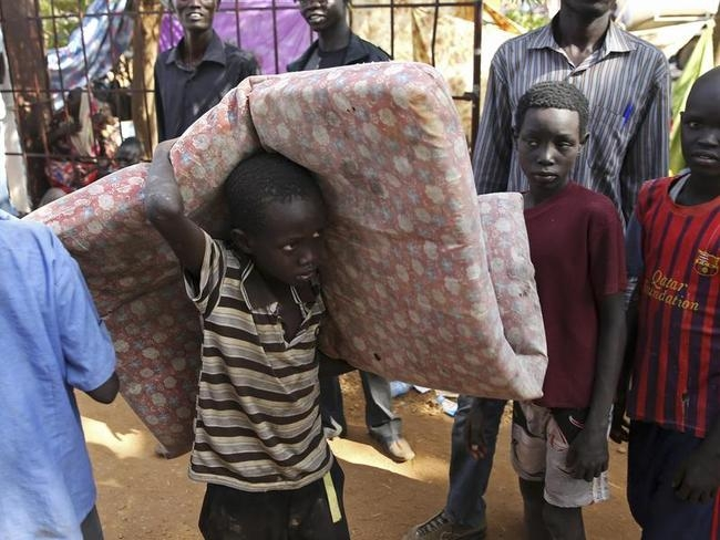 An internally displaced boy carries his belongings inside a UNMIS compound in Juba