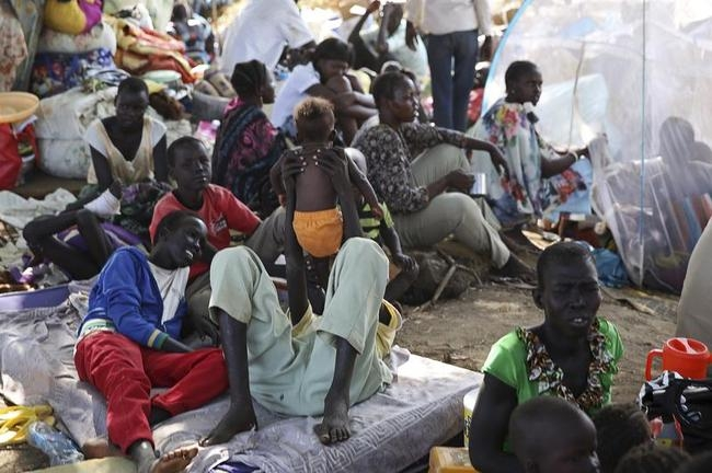 An internally displaced man plays with his child inside a UNMIS compound in Juba