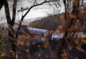 A man in a kayak paddles past the site of a Metro North train derailment in the Bronx borough of New York