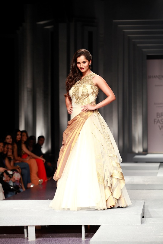 Sania Mirza glided in gracefully wearing a white net one-shoulder gown with gold drapes and embroidery scattered over the bodice.