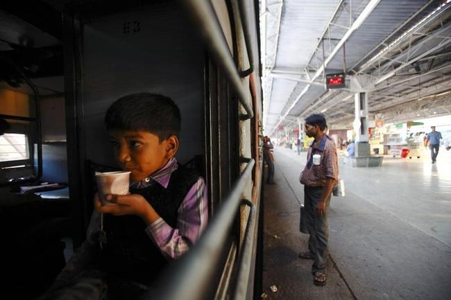 A boy drinks tea inside a train at Agra Cantt Railway Station in Agra