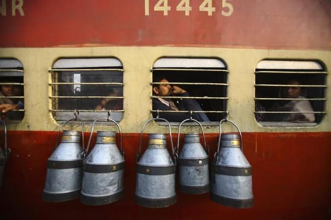 Empty milk containers hang from the window of a train in Uttar Pradesh