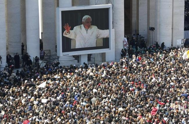 Pope Benedict XVI appears on a giant screen in a packed Saint Peter