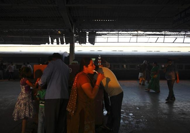 A woman brushes her teeth after her train stopped at Agra Cantt Railway Station in Agra
