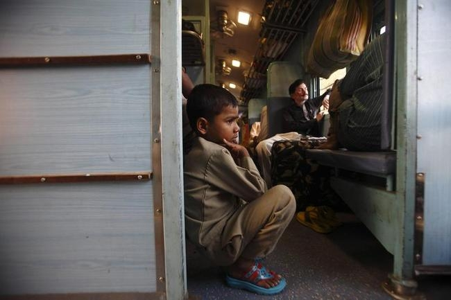A child sits on the floor of a train heading towards Allahabad from Kanpur in Uttar Pradesh