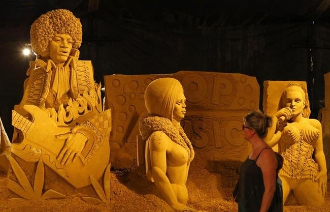 A woman looks at sculptures representing Jimmy Hendrix and Madonna during the Sand Sculpture Festival in Blankenberge, northern Belgium