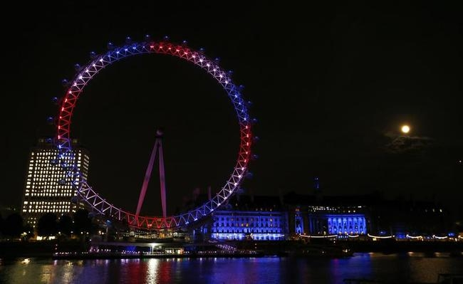The London Eye is lit in red, white and blue and the full moon is visible after Catherine, Duchess of Cambridge gave birth to a baby boy at St Mary