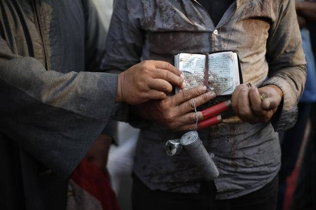 A wounded supporter of deposed Egyptian President Mohamed Mursi holds empty bullet shells and the Koran outside the Rabaa Adawiya mosque in Cairo