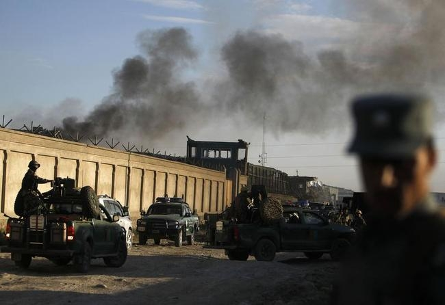Afghan security forces keep watch as smoke rises from the site of an attack in Kabul