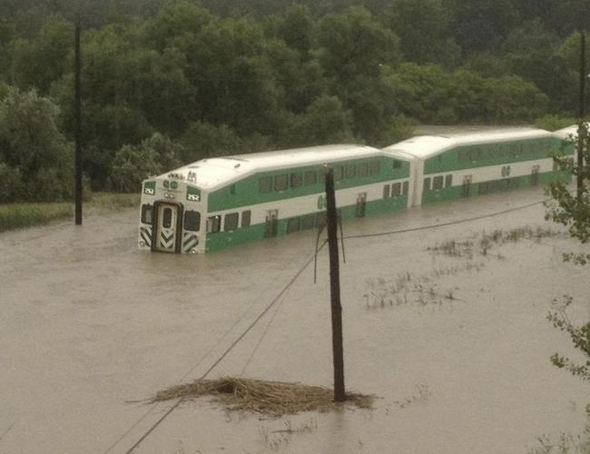 A Go Train, a commuter train, headed for Richmond Hill sits submerged in flood water during a severe rain storm in Toronto