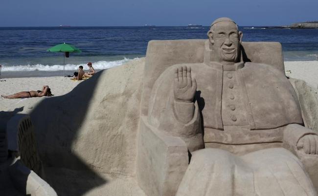People sunbathe behind a Pope Francis sand sculpture at Copacabana beach in Rio de Janeiro