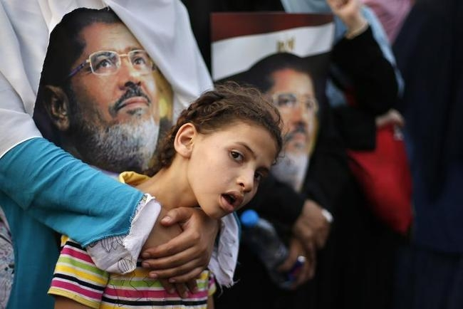 Supporter of deposed Egyptian President Mohamed Mursi attends a protest outside the Rabaa Adawiya mosque in Cairo
