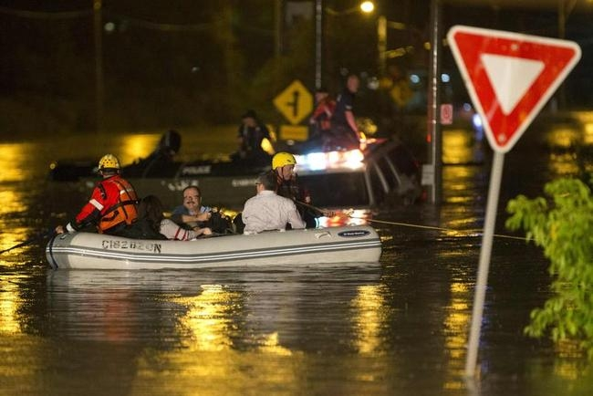 Dingy full of passengers that were stranded on Go Train, a commuter train that was stopped on its tracks due to a flood, are rescued during heavy rainstorm in Toronto