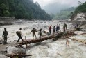 Indian army personnel help stranded people cross a flooded river after heavy rains in the Himalayan state of Uttarakhand