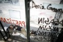 A protester sleeps at a bus stop sprayed with graffiti at Taksim Square in Istanbul