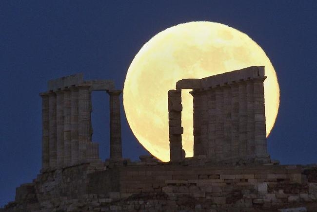 The moon rises over the temple of Poseidon in Cape Sounion east of Athens
