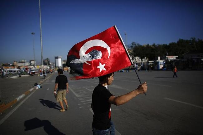 A protester holds a Turkish national flag with the image of Ataturk, founder of modern Turkey, on it at Taksim Square in central Istanbul
