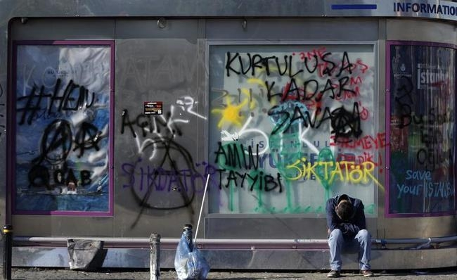 A man sleeps in front of the graffiti sprayed wall of an information center booth at Taksim Square in central Istanbul