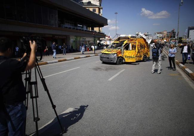 TV crews film near a damaged broadcaster