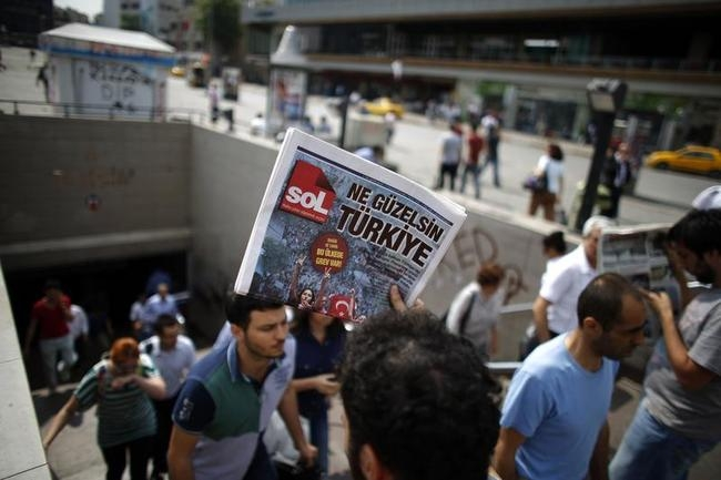 A man sells newspapers to people as they leave the subway station at Taksim Square in Istanbul