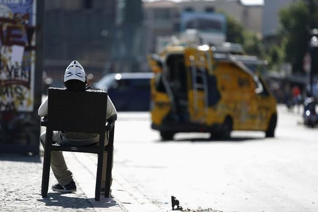 A protester wearing a Guy Fawkes mask sleeps on a chair at Taksim Square in central Istanbul