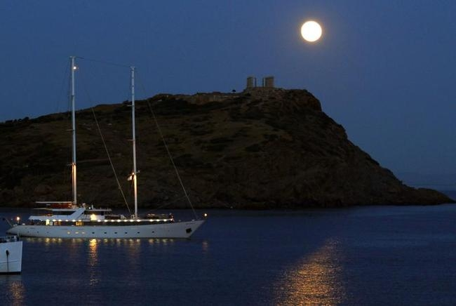 A supermoon rises over the temple of Poseidon, the ancient Greek god of the seas, in Cape Sounion, east of Athens
