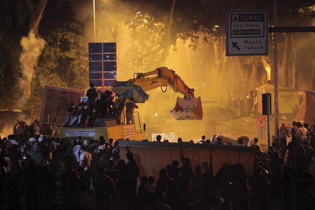 Anti-government protesters behind the barricades and on an excavator clash with riot police as they try to march to the office of Turkey