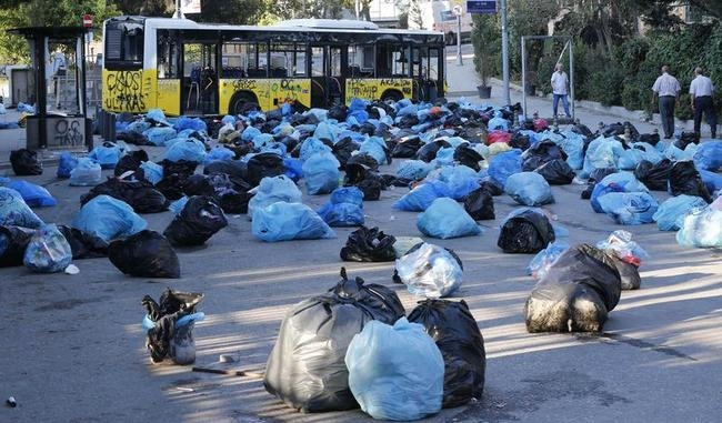 Garbage bags are strewn all over a street by protesters to form a barrier near a damaged bus after demonstrations in Istanbul
