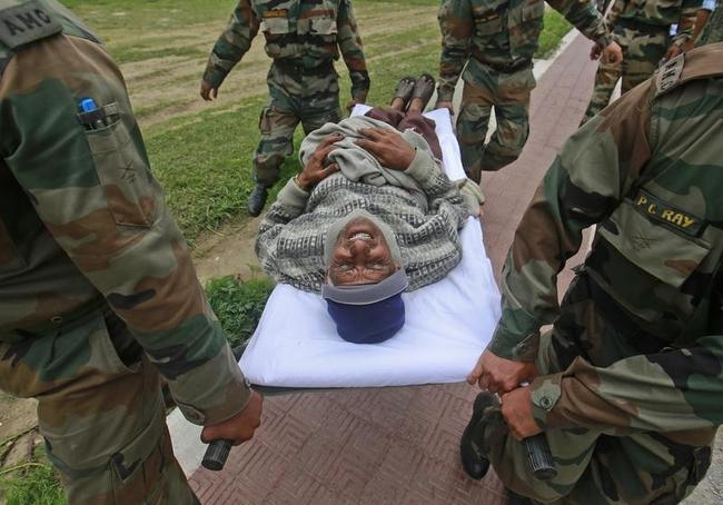 A man cries in pain as he is carried away by soldiers from an army helicopter during a rescue operation at Joshimath in the Himalayan state of Uttarakhand
