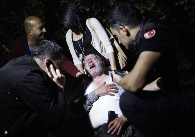 Riot policemen try to help a protester who was injured during clashes in Kennedy street in central Ankara