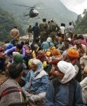 Stranded people wait for their turn to be rescued by a helicopter after heavy rains in the Himalayan state of Uttarakhand