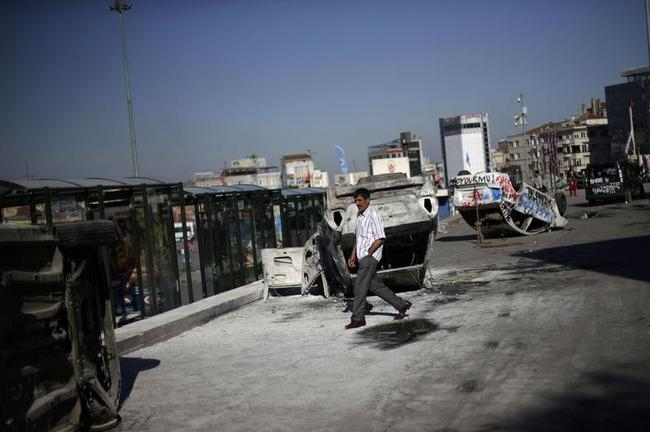 A man walks past damaged cars at Taksim Square in central Istanbul