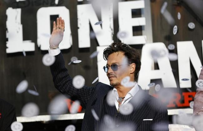 """Cast member Johnny Depp waves as confetti fly at the world premiere of """"The Lone Ranger"""" in Anaheim"""
