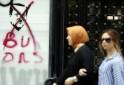 Women walk past graffiti depicting Turkish PM Erdogan in Istanbul
