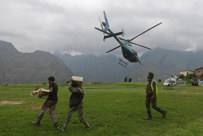 Soldiers carry boxes of relief supplies as an army helicopter flies overhead during a rescue operation at Joshimath in the Himalayan state of Uttarakhand