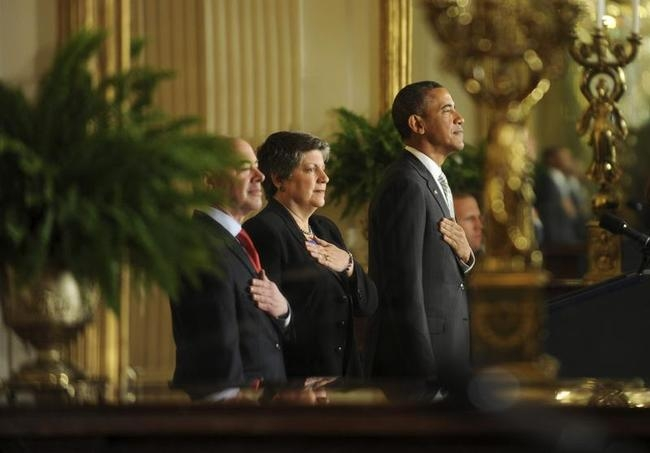 Mayorkas, Napolitano and Obama are seen reflected in a mirror as they attend a naturalization ceremony for active duty service members and civilians in the East Room at the White House in Washington