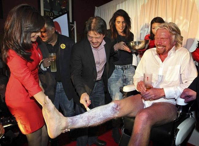 British entrepreneur Branson gets his legs shaved during an AirAsia promotional event in Perth